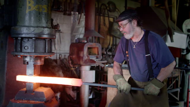 Side view of blacksmith working metal bar in slow motion video