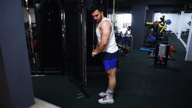 vídeos de stock e filmes b-roll de side view of bodybuilder doing arm exercise - músculo humano