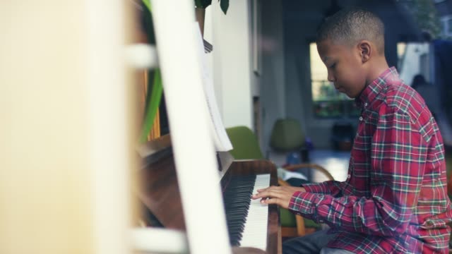 side view of boy playing piano at home - praticare video stock e b–roll