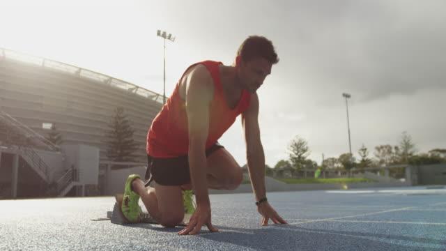 widok z boku kaukaskiego sportowca przygotowującego się do wyścigu na stadionie - start filmów i materiałów b-roll