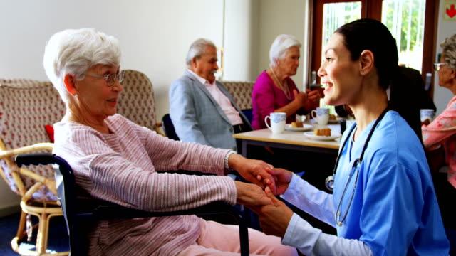 白人女性医師慰め悲しい障害を持つ老人ホーム4k の側面図 - 老人ホーム点の映像素材/bロール