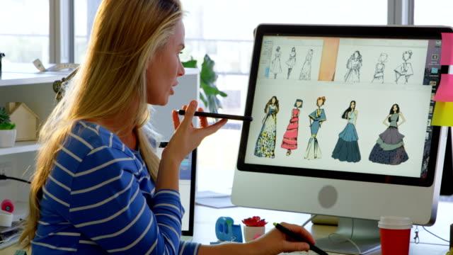 vídeos y material grabado en eventos de stock de vista lateral del diseñador de moda femenina caucásica hablando en el teléfono móvil en la oficina 4k - moda preppy