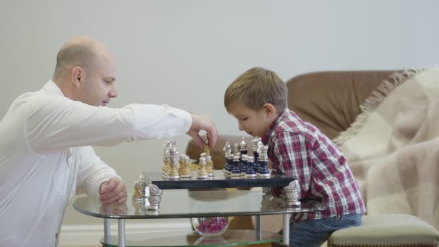 Side view of Caucasian man in white shirt sitting in front of chess board and playing with clever son. Cute smart boy spending free tine with father at home. Unity, intelligence, education.