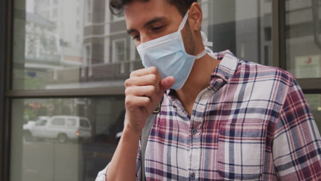 Side view of Caucasian man wearing a corovirus covid19 mask and coughing
