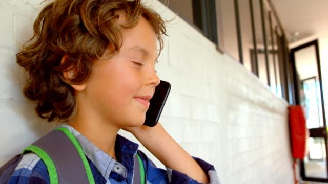 Side view of Caucasian schoolboy talking on mobile phone in school corridor 4k