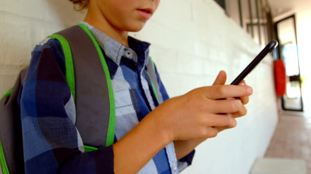 Side view of Caucasian schoolboy using mobile phone while leaning on wall in school corridor 4k
