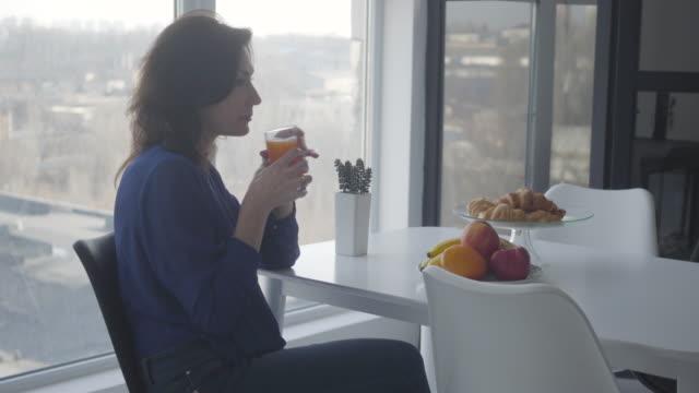 sidovy av säker kaukasisk kvinna luktar apelsinjuice och tar frukt. förmögen affärskvinna som äter frukost ensam hemma. ensamhet, sorg, livsstil. - endast unga kvinnor bildbanksvideor och videomaterial från bakom kulisserna