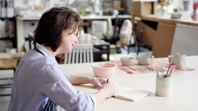 Side view of creative ceramic artist sitting at desk in studio, drawing in sketchbook and smiling dreamily