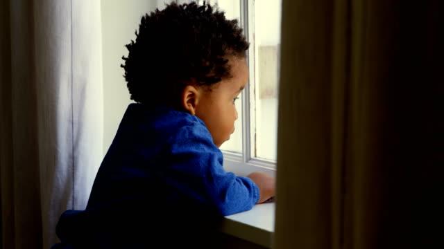 side view of cute little black boy leaning on window sill in a comfortable home 4k - neonati maschi video stock e b–roll