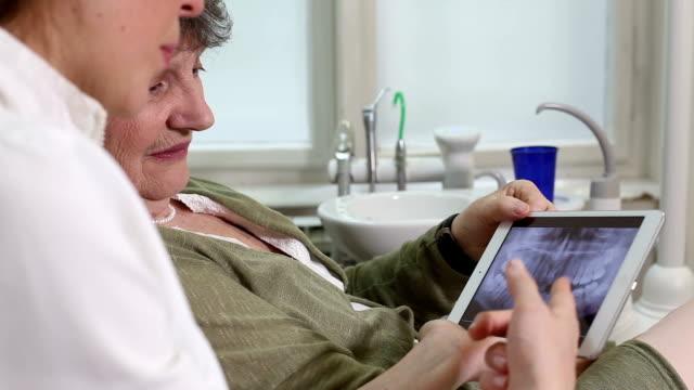 sidovy av tandläkare som visar röntgen tänder på surfplattan till sin patient - two dentists talking bildbanksvideor och videomaterial från bakom kulisserna