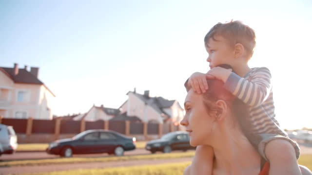 Side view of family spending time together on a sunny summer day. Cute little boy sits on his moms shoulders. Slow mo video