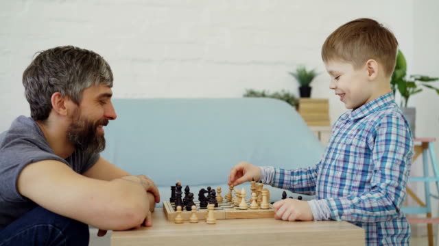 seitenansicht von vater und sohn zu hause schach spielen, reden und lachen. schachbrett mit schwarzen und weißen spielmarke, grünpflanzen und modernen möbeln sind sichtbar. - bauholz brett stock-videos und b-roll-filmmaterial