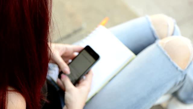 seitenansicht der weibliche college student textnachrichten auf dem campus - amerikanische geldmünze stock-videos und b-roll-filmmaterial