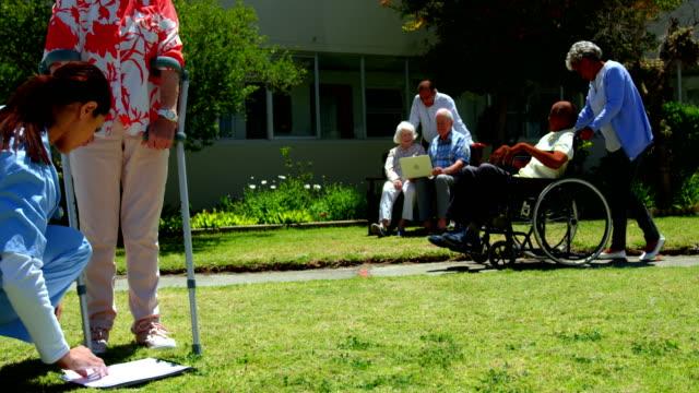 養護老人ホーム 4 k の庭でシニア患者を調べる女性医師の側面図 - 介護点の映像素材/bロール