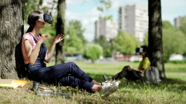 Side view of female student in VR headset swiping visualized data sitting under tree in park. Another college girl wearing virtual reality glasses in background
