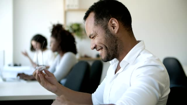 Side view of focused young man typing on laptop then laughing