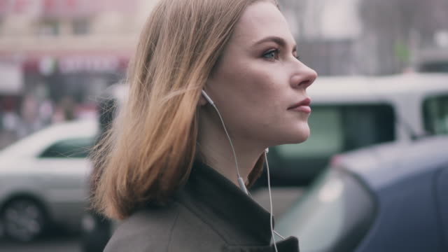 Side view of girl in headphones walking on the street video