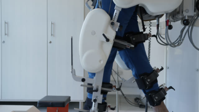 Side view of handsome man walking on treadmill with the help of a exoskeleton robot during therapy Side view of handsome man walking on treadmill with the help of a exoskeleton robot during therapy - Technology concepts prosthetic equipment stock videos & royalty-free footage