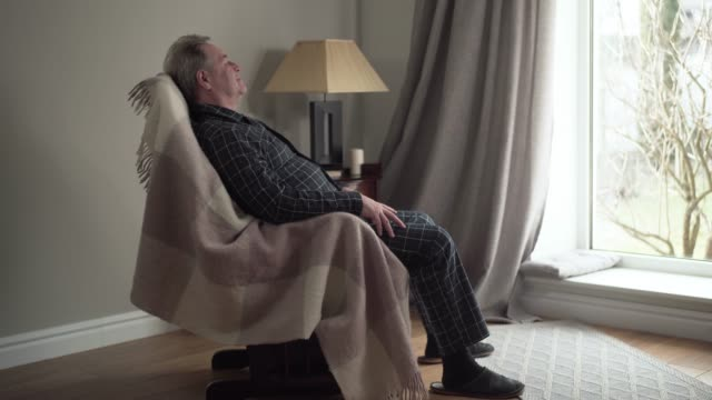 Side view of happy mature Caucasian man swinging in rocking chair at home. Smiling senior retiree looking out the window and thinking. Wide shot. Retirement, leisure, lifestyle Side view of happy mature Caucasian man swinging in rocking chair at home. Smiling senior retiree looking out the window and thinking. Wide shot. Retirement, leisure, lifestyle rocking chair stock videos & royalty-free footage