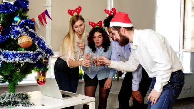 会議の呼び出しを行うと本社オフィス パーティーでスパーク リング ワイン付きのガラスをチリンとサンタ帽子で幸せなチームの側面図です。オフィスの企業パーティー。国際的なチーム - サンタの帽子点の映像素材/bロール