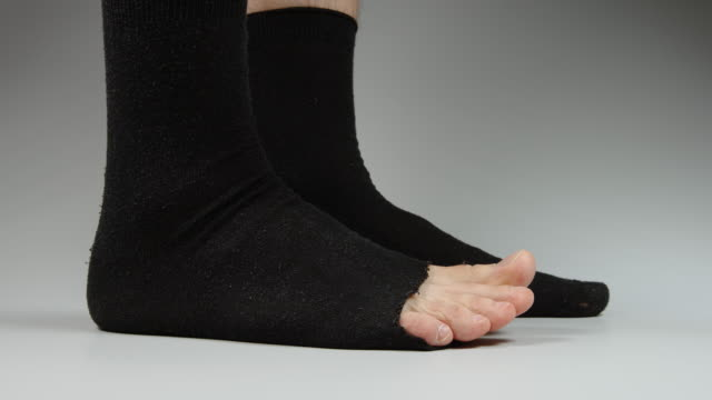 side view of male legs with socks with a hole - calzino video stock e b–roll