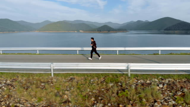Side view of man jogging in the morning on lake and mountain view video