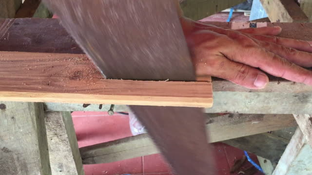 Side view of man sawing wood plank video