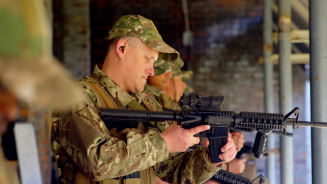 Side view of mixed-race military soldiers loading weapon during training 4k Side view of mixed-race military soldiers loading weapon during training. They are loading magazine in rifle 4k mixed race person stock videos & royalty-free footage