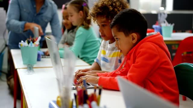 sınıf 4k dizüstü bilgisayarda okuyan karışık yarış okulların yan görünümü - okul çocukları stok videoları ve detay görüntü çekimi
