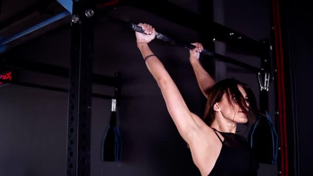 seitenansicht der muskulösen erwachsenen sportlerin in schwarzen leggings und bh, der an der metallstange im fitnessstudio hängt und mit klimmuppen bestimmt wird. - turngerät mit holm stock-videos und b-roll-filmmaterial