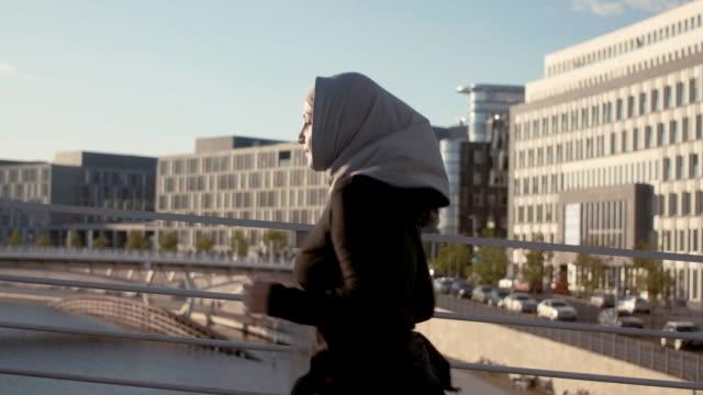 sidovy av muslimsk kvinna i hijab kör i solnedgången (slow motion) - hijab bildbanksvideor och videomaterial från bakom kulisserna