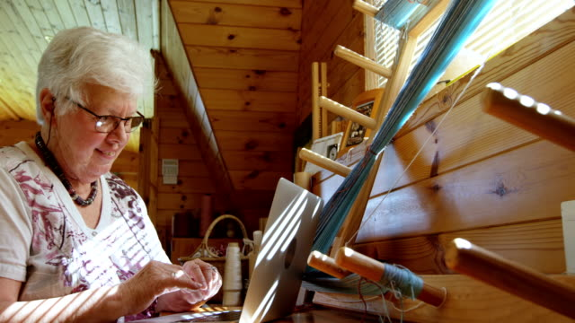 side view of old caucasian senior woman working on laptop and sitting at desk in workshop 4k - 60 69 anni video stock e b–roll