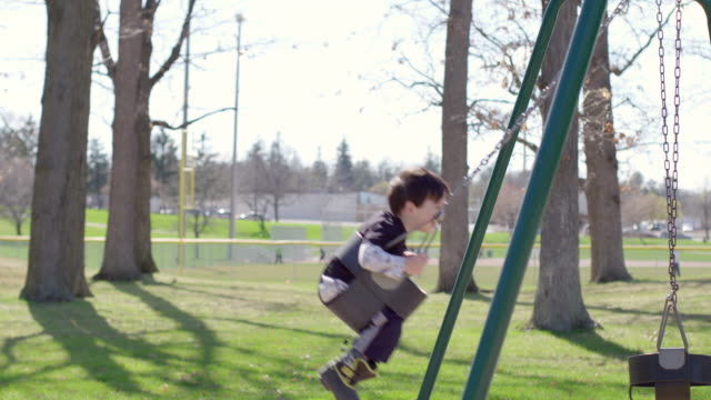 Side view of playground swings with boy swinging backward in and out video