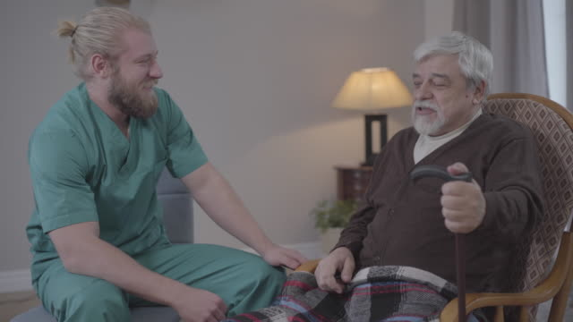 Side view of positive male nurse and retiree talking and laughing. Caucasian adult and mature men spending happy evening in nursing home. Joy, leisure, happiness.
