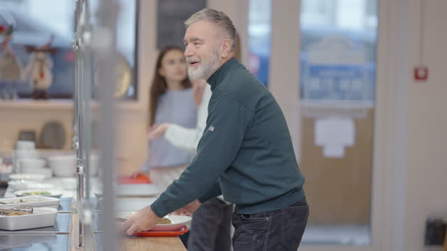 Side view of positive senior man ordering food in cafeteria talking and smiling. Bearded Caucasian retiree in queue at lunch in dining room. Lifestyle and eating concept.