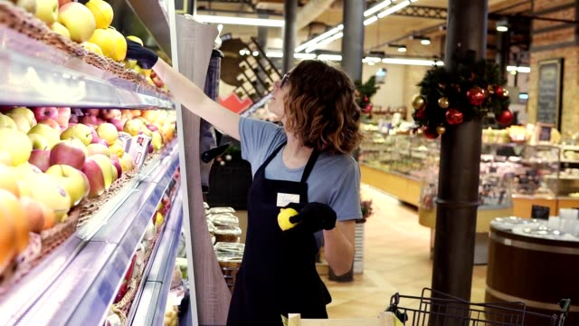 Side view of pretty caucasian worker in black apron and gloves stocking the fruits in supermarket. Young employee at work. Curly female arranging fruits on shelf video