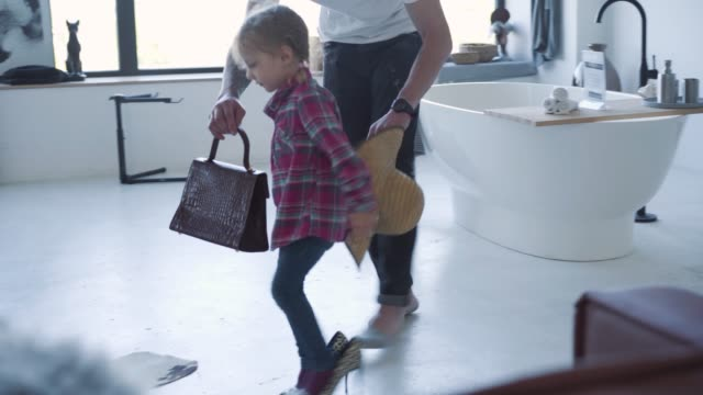 Side view of pretty little girl in high-heels walking from father to mother. Caucasian stylish child enjoying weekends with parents at home. Bonding, family, unity, lifestyle, leisure.
