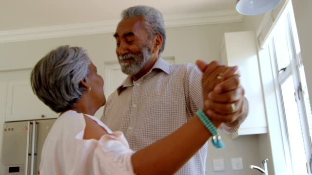 side view of senior black couple dancing together in kitchen at comfortable home 4k - 60 64 года стоковые видео и кадры b-roll