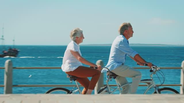 seitenansicht des älteres paar reiten tandem-fahrrad - aktiver senior stock-videos und b-roll-filmmaterial