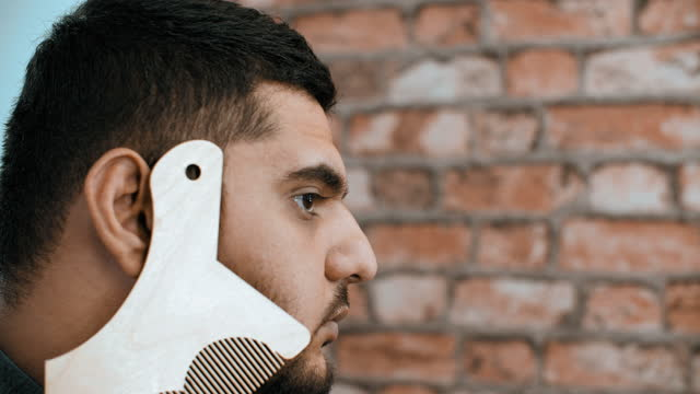 Side view of serious man using beard stencil template