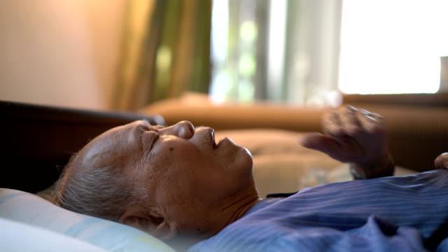 vídeos de stock e filmes b-roll de side view of sick senior man on bed at home - doença