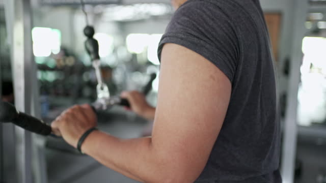 side view of skinhead man working out his triceps at gym
