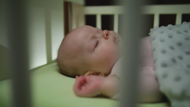 vidéos et rushes de vue latérale du sommeil de bébé nouveau-né dolly tourné close up - allongé sur le dos