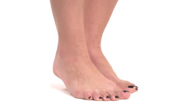vídeos de stock, filmes e b-roll de vista lateral de pés fêmeas magros com pedicure preta à moda que está nos dedos do pé. isolado, no fundo branco - pedicure