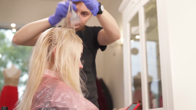eine seitenansicht der blondine sitzt beim friseur. der friseur steht hinter, nimmt stränge und haarfärbemittel gilt. - haartönung stock-videos und b-roll-filmmaterial