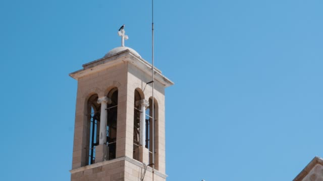 Side view of the top of city church with bell tower against a blue clear sky. Close up view of white belfry