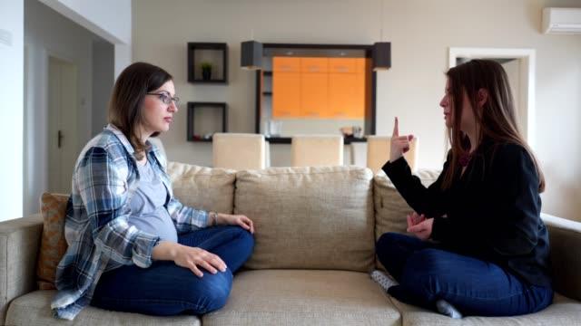 vídeos de stock, filmes e b-roll de opinião lateral o sinal surdo de dois amigos que fala em um sofá - surdo
