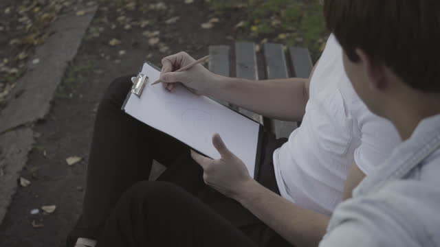 Side view of two unrecognizable young Caucasian men drawing design sitting on bench outdoors. Male architects planning project. Occupations and professions concept
