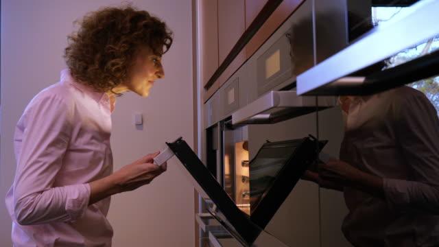 vidéos et rushes de vue de côté de femme vérifiant les aliments dans le four - four
