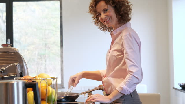 vídeos de stock e filmes b-roll de side view of woman cuooking in the kitchen - cooker happy